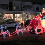 Santa's sleigh parks in front of the rowhomes